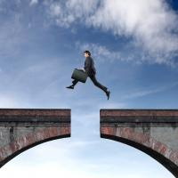 man jumping over hole in bridge