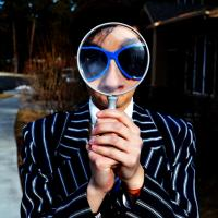 Person holding magnifying glass, photo by Mar Newhall