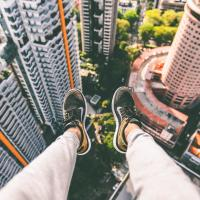 A person's legs dangling off the edge of a building, photo by Alex Wong