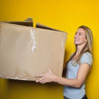 Smiling woman holding a large box, photo by bruce mars