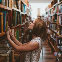 Woman looking for a book in the shelves of a library, photo by Clay Banks