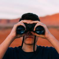 Photo of a person looking through binoculars, by Evan Kirby