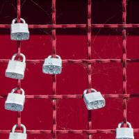 Locks on a red fence, photo by Jon Moore