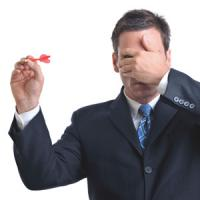 Man covering his eyes while throwing a dart