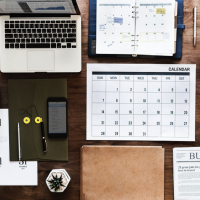 An organized desk with computer, planner, calendar, and more