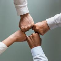 Four people fist-bumping in a workspace