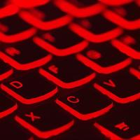 A computer keyboard lit up red, photo by Taskin Ashiq