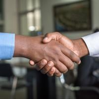 Two people shaking hands after earning a promotion
