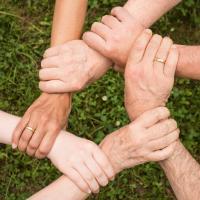 Testing team interlocking their hands in support