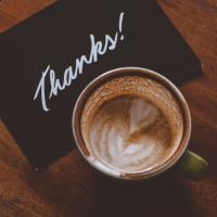 Thank-you card next to a cup of coffee