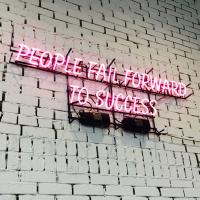 """Neon sign saying """"People fail forward to success"""""""