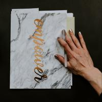 "Person's hand on a folder with the word ""empower"" on it, containing evaluations"