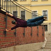 An agile acrobat holds himself perpendicular to a wall
