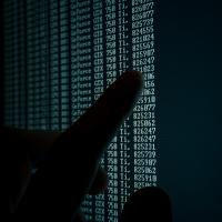 Hand pointing at data on a screen
