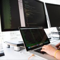 Person typing with multiple monitors up with different programming languages