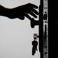 Silhouette of person unlocking a door with keys
