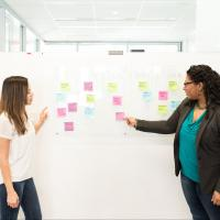 Two agile teammates using a kanban board with sticky notes