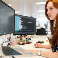 Software engineer looking at her computer monitors and integrating code