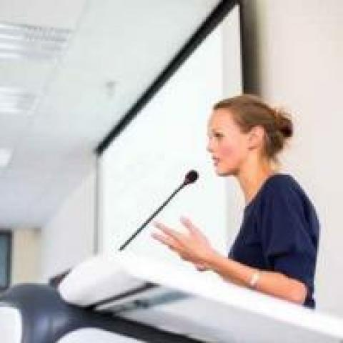 Woman at a podium giving a presentation