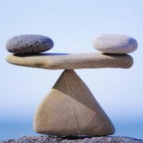 Two rocks balancing on another rock acting as a fulcrum
