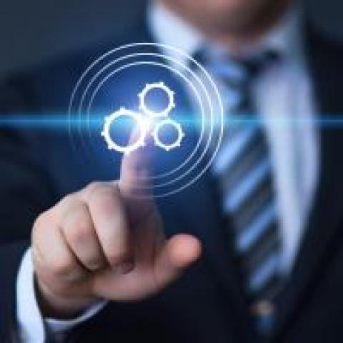 Businessman touching a gears icon for automation