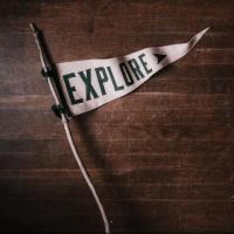 "White flag that says ""EXPLORE,"" photo by Andrew Neel"