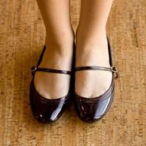 Woman's feet standing on a wood floor