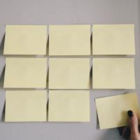 Person adding a square to a grid of sticky notes, photo by Kelly Sikkema