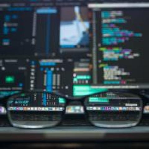 A pair of eyeglasses in front of a computer with code on the screen