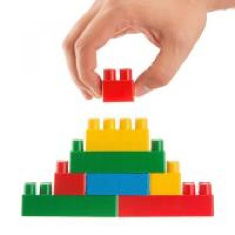 Hand putting together units of Legos