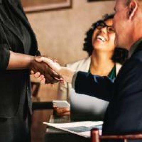 Woman shaking hands with a job candidate after a hiring interview