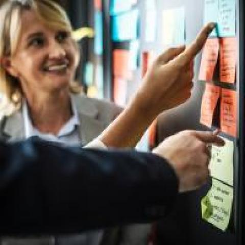 Project manager smiles while pointing to action items on sticky notes