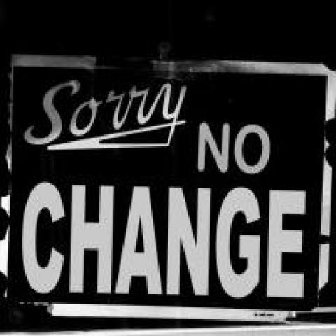 """Sign in shop window that says """"Sorry, no change"""""""