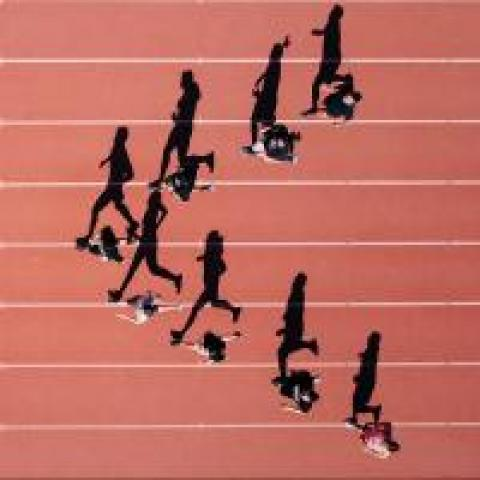 People running on a track with a leader in front
