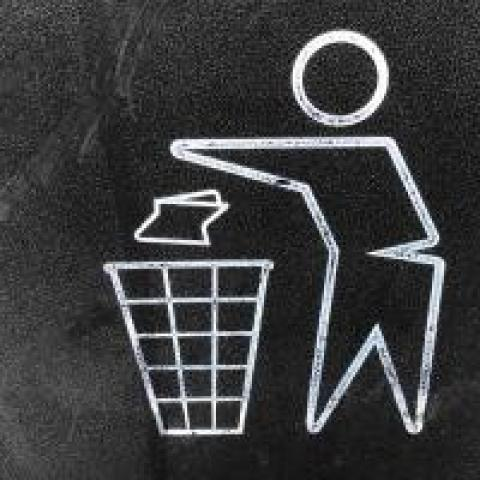 Icon of a person throwing garbage into a trash can
