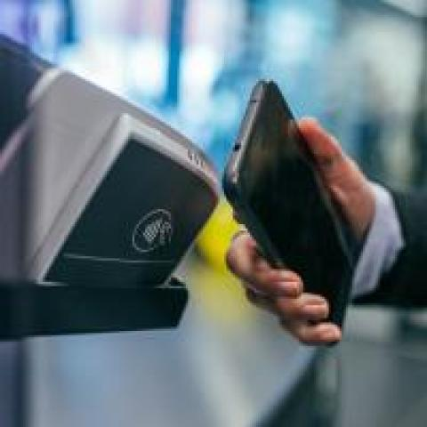 Person making a mobile payment using contactless card technology by waving an Android phone in front of an NFC reader