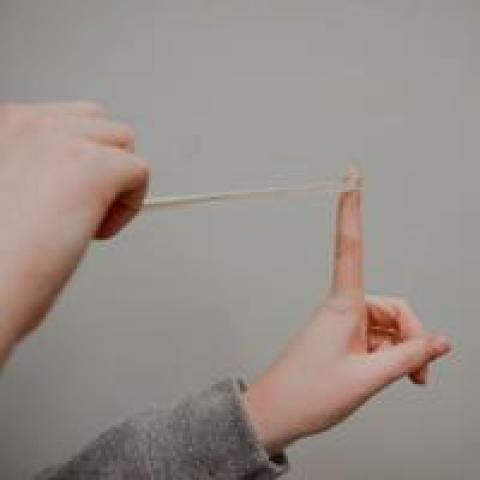 Person about to shoot a rubber band at a coworker